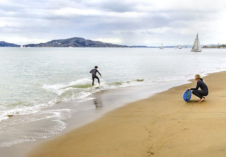 View of a surfer in wet suit surfing his board or skimboarding in shallow water in the San Francisco Bay, on the beach coast, sailboats and yachts crossing the sea from Marina neighborhood in California, United States.