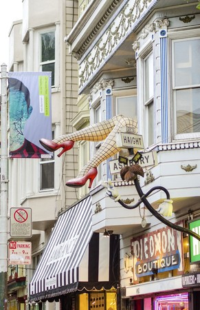 Haight Ashbury neighborhood in San Francisco, California, United States of America, a hippy area. View of a sculpture with large legs wearing fishnet stockings and red stiletto heel shoes out of a shop window.