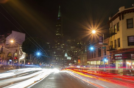 A night view of Little Italy at the intersection of Columbus and Broadway in North Beach, San Francisco, California, United States of America. View of Transamerica pyramid, italian restaurants, city and car light trails.