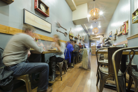 A hipster, vintage, retro, rustic yet modern cafe restaurant in San Francisco, California. A view of the interior decoration and people drinking and eating inside the coffee shop.