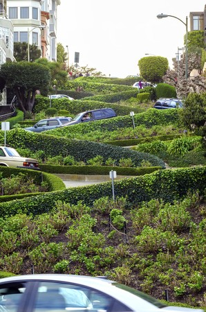 The famous Lombard street on Russian Hill in San Francisco, California, United States of America. A view of the crooked road with curves and turns, the houses and garden around it.