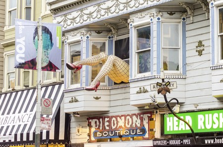 castro: Haight Ashbury neighborhood in San Francisco, California, United States of America, a hippy area. View of a sculpture with large legs wearing fishnet stockings and red stiletto heel shoes out of a shop window.