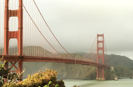 san francisco golden gate bridge: The famous San Francisco Golden Gate Bridge in California, United States of America. A view of the Bay and the red suspended bridge connecting Frisco to Marin County at sunset against a cloudy sky. Stock Photo