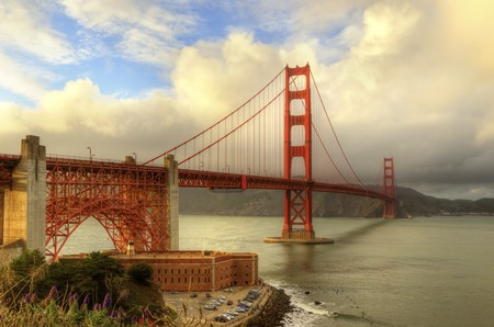 frisco: The famous San Francisco Golden Gate Bridge in California, United States of America. A view of Fort Point, the bay, surfers and the red suspended bridge connecting Frisco to Marin County at sunset.