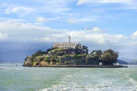 The Alcatraz Penitentiary, now a museum, in San Francisco, California, United States of America. A view of the island, the lighthouse, prison buildings and the San Francisco Bay from the coast on a sunny day.