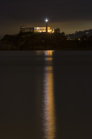 The Alcatraz Penitentiary island, now a museum, in San Francisco, California, United States of America. A night view of light reflected in the sea from the lighthouse, prison buildings and the San Francisco Bay.