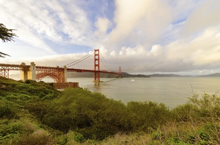 frisco: The famous San Francisco Golden Gate Bridge in California, United States of America. A view of the Bay and the red suspended bridge connecting Frisco to Marin County at sunset against the pink sky. Stock Photo