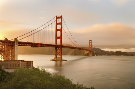 frisco: The famous San Francisco Golden Gate Bridge in California, United States of America. A view of the Bay, Fort point and the red suspended bridge connecting Frisco to Marin County at sunset against the pink sky. Stock Photo
