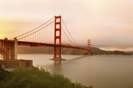 marin: The famous San Francisco Golden Gate Bridge in California, United States of America. A view of the Bay, Fort point and the red suspended bridge connecting Frisco to Marin County at sunset against the pink sky. Stock Photo