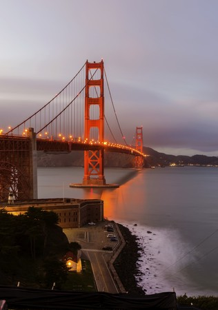 san francisco golden gate bridge: The famous San Francisco Golden Gate Bridge in California, United States of America. A long exposure of Fort Point, the bay and the illuminated red suspended bridge at night looking as if on fire. Editorial