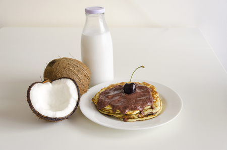 open topped: Breakfast and brunch coconut pancakes meal with cracked open coco, glass bottle of milk and cherry on white background. Stack of crepes is topped with cream syrup ready to eat.