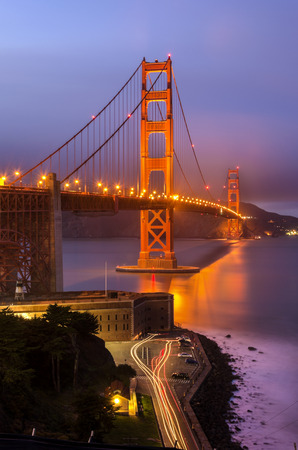 san francisco golden gate bridge: The famous San Francisco Golden Gate Bridge in California, United States of America. A long exposure of Fort Point, the bay and the illuminated red suspended bridge at night looking as if on fire. Stock Photo