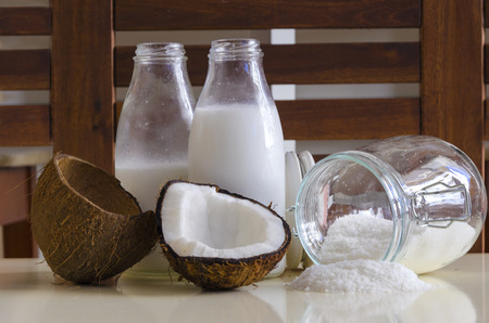 grounded: Coconut products. Cracked open coconut with meat cut in half, grounded flakes in a mason jar, flour and fresh milk in glass bottles on a table with wooden background. Stock Photo