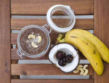 breakfast bowl: Cherry coconut banana overnight oats with cracked open coco, banana, cashews mixed with chia seeds and cherry cream in a mason jar, tropical meal on top view wooden background. Healthy fitness breakfast oatmeal.
