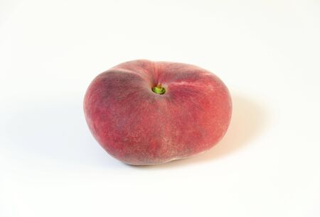 peen: A whole, medium-size, ripe, juicy saturn peach shaped like a donut with a sunken middle, white skin with red blush isolated on background. An oddly doughnut like flat round peach yet tasty. Stock Photo