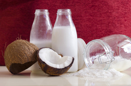 grounded: Coconut products. Cracked open coconut with meat cut in half, grounded flakes in a mason jar, flour and fresh milk in glass bottles on a table with red ruby background.