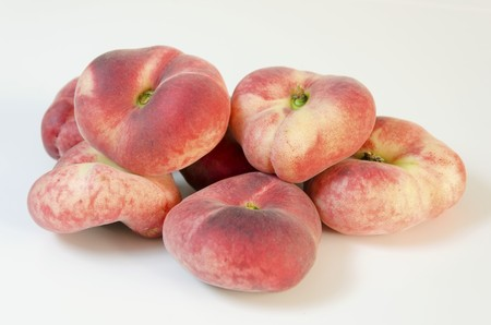 peen: Six whole, medium-size, ripe, juicy saturn peaches shaped like a donut with a sunken middle, white skin with red blush isolated on background. An oddly doughnut like flat round peach yet tasty.