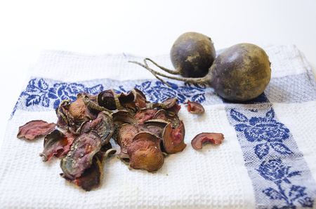 appetiser: Thin round beetroot chips baked in the oven with oregano and salt and ripe beet roots in the white background. A healthy, vegetarian, vegan, crispy snack appetiser for diet and clean eating.