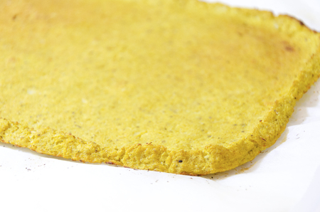 pizza crust: Rectangular cauliflower pizza crust with selective focus on edge. A healthy low carb, gluten free, vegan, vegetarian snack with grated cauli flower baked in the oven isolated on white background on parchment baking paper