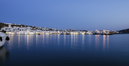 myconos: Night view of Chora and the port in Mykonos, Greece. Hora town cityscape lights reflected on the sea, whitewashed greek island houses in the harbour and yachts anchored. A colourful and beautiful seascape.