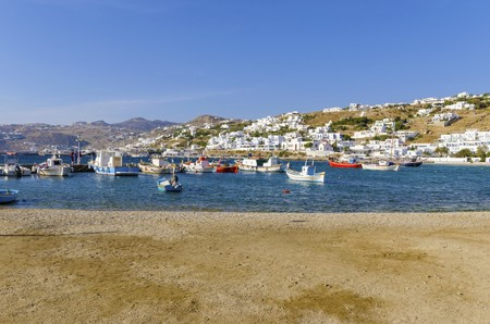 myconos: Colourful fishing and sail boats anchored on the Chora port in Mykonos, Greece. A view of a typical greek island harbour, golden sandy beach, whitewashed buildings on the hill and blue sea on a sunny day