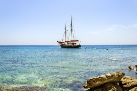 A traditional wooden sail boat anchored on the coast of Mykonos, Greece. The wind sails are down and it is tied on the rocks by a rope. A very typical greek island summer holiday scene on crystal clear blue sea. 스톡 콘텐츠