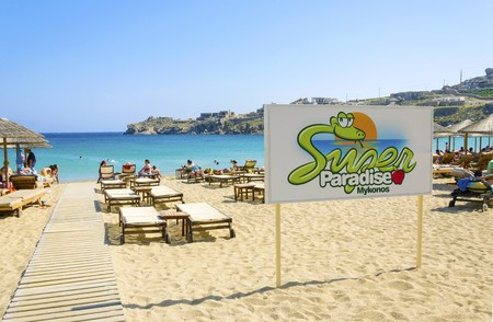snake bar: The famous Super paradise beach on the greek island Mykonos, Greece. A view of the golden sandy beach, the sign, sunbeds, umbrellas and blue sea in a perfect summer holiday party place.