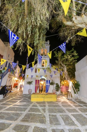 myconos: A christian greek orthodox church at easter in Chora, Mykonos, Greece. A traditional greek island easter scene, decorated with flags of the religion and a ceremony in whitewashed chapel and cobbled paved alley.