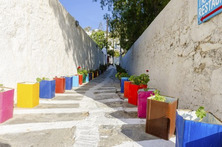chora: A typical greek island cobbled alley in Chora, Mykonos, Greece decorated with colourful flower pots of geranium and surrounded by whitewashed architecture.