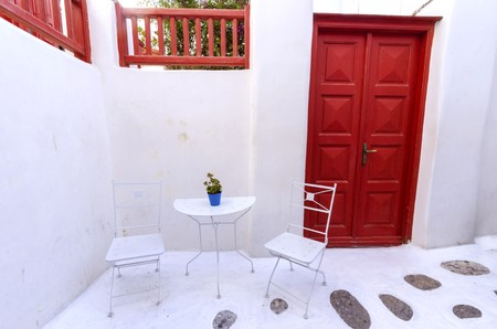 myconos: A very traditional alley view of the architecture in Chora, on the greek island Mykonos, Greece. A red door and fence and white chairs and tables outside a whitewashed house and cobble paved street.