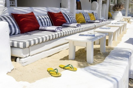 greek island: A summer beach bar restaurant, lounge on the beach of Psarou in Mykonos, Greece. A view of the sofas, tables and flip flops on golden sand offering a relaxing holiday atmosphere on a greek island.