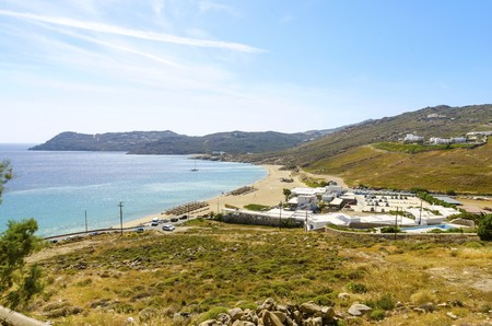 myconos: Aerial view of Elia beach on greek island Mykonos, Greece. A view of the blue sea, sunbeds, sun umbrellas, golden sand and whitewashed houses on a summer day. Stock Photo