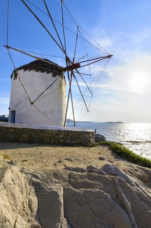 myconos: A windmill in Chora, Mykonos, Greece. Very traditional greek whitewashed architecture, a popular landmark and tourist destination on the island of winds against the deep blue sky and the Aegean sea. The wind mills are now decorative. Stock Photo