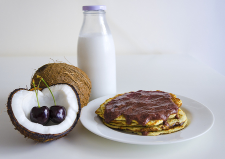 Breakfast and brunch coconut pancakes meal with cracked open coco, glass bottle of milk and cherry on white background. Stack of crepes is topped with cream syrup ready to eat.