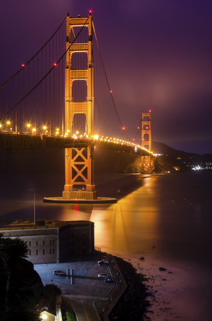 red cross red bird: The famous San Francisco Golden Gate Bridge in California, United States of America. A long exposure of Fort Point, the bay and the illuminated red suspended bridge at night looking as if on fire. Stock Photo