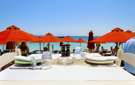 myconos: A table set with plates, glasses and napkins on a beach bar restaurant and a view of the sun umbrellas and the blue sea in Mykonos, Greece. A greek island scene at the beach. Editorial
