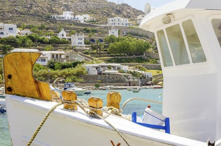 myconos: Fishing boats docked at Ornos beach in Greece. A view of the crystal clear blue sea at the greek island Mykonos, and whitewashed houses on the hill slope. A typical, idyllic summer holiday beach scene.