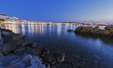 myconos: Night view of Chora and the port in Mykonos, Greece. Hora town cityscape lights reflected on the sea, whitewashed greek island houses in the harbour and rocks on calm water. A colourful and beautiful seascape.