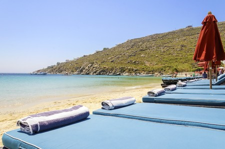 myconos: Sun beds with couchins, towels, umbrellas, golden sand and the blue sea in Mykonos, Greece. A greek island summer holiday scene at the Psarou beach with a boat in the crystal clear water over a bushy hill.