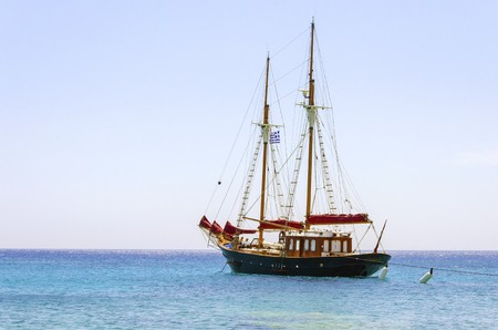 myconos: A traditional wooden sail boat anchored on the coast of Mykonos, Greece. The wind sails are down and it is tied on the rocks by a rope. A very typical greek island summer holiday scene on crystal clear blue sea. Stock Photo