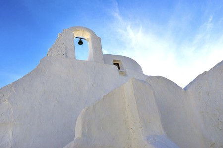 myconos: Panayia Paraportiani church in Mykonos island, Greece. A very typical, traditional, whitewashed christian greek orthodox chapel with dome in Little Venice in Chora against blue sunny sky.