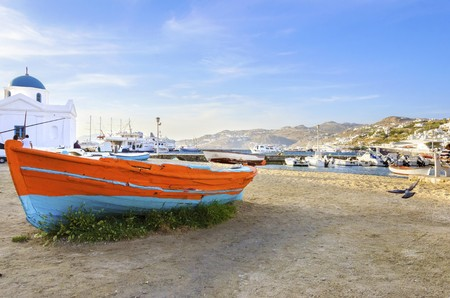 myconos: Colourful fishing and sail boats anchored on the Chora port in Mykonos, Greece. A view of an orange and blue boat on the sand shore and the whitewashed. blue dome church of Hora harbour, a typical greek island landscape.