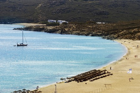 super yacht: Aerial view of Elia beach on greek island Mykonos, Greece. A view of the blue sea, sunbeds, sun umbrellas, golden sand and a sailboat in the water on a summer day. Stock Photo