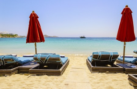 Sun beds with couchins, umbrellas, golden sand and the blue sea in Mykonos, Greece. A greek island summer holiday scene at the Psarou beach with a boat in the crystal clear water.