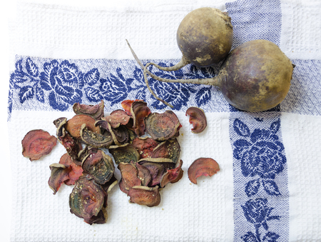 appetiser: Top view of thin round beetroot chips baked in the oven with oregano and salt and ripe beet roots in the white background. A healthy, vegetarian, vegan, crispy snack appetiser for diet and clean eating.