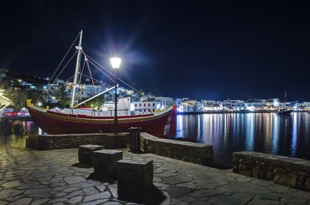 whitewashed: Night view of Chora and the port in Mykonos, Greece. Hora town cityscape lights reflected on the sea, whitewashed greek island houses in the harbour and a sail boat on the shore. A colourful and beautiful seascape. Stock Photo
