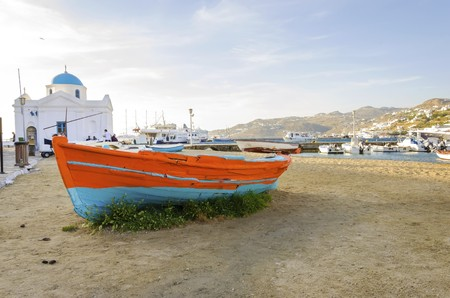 whitewashed: Colourful fishing and sail boats anchored on the Chora port in Mykonos, Greece. A view of an orange and blue boat on the sand shore and the whitewashed. blue dome church of Hora harbour, a typical greek island landscape.