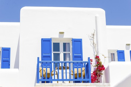 myconos: A trational whitewashed cubic beach greek island holiday apartment with blue wooden windows and blacony, red bougaivillea facing the sea in Mykonos, Greece on a summer day