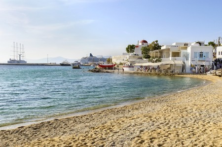 whitewashed: The coastline of Chora in Mykonos, Greece. Typical greek island whitewashed houses on the shore and seaview golden sand promenade overlooking the Aegean sea and calm clean blue water.