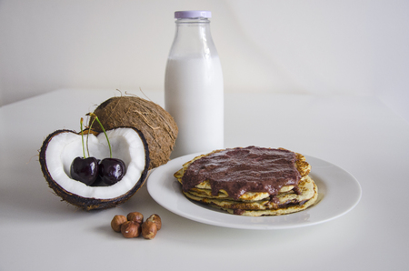 open topped: Breakfast and brunch coconut pancakes meal with cracked open coco, glass bottle of milk and cherry on white background. Stack of crepes is topped with cream syrup and hazelnuts ready to eat. Stock Photo